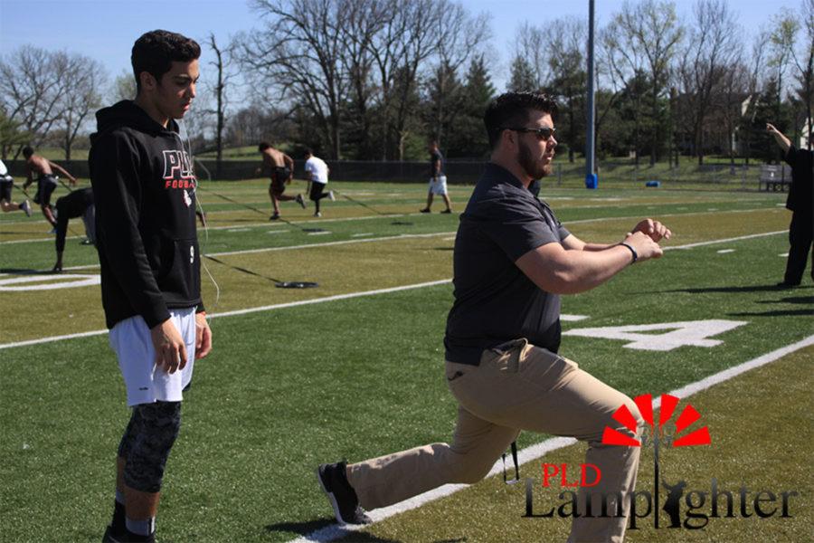 Athletic trainer Cody Begley demonstrating an exercise for injured athlete Landon Jackson to do.