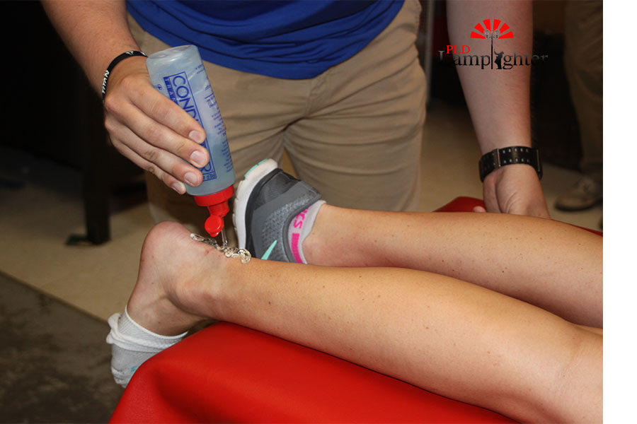 Cody Begley, Dunbar's athletic trainer putting cooling gel on Cheerleader Macy Backer's injured ankle.