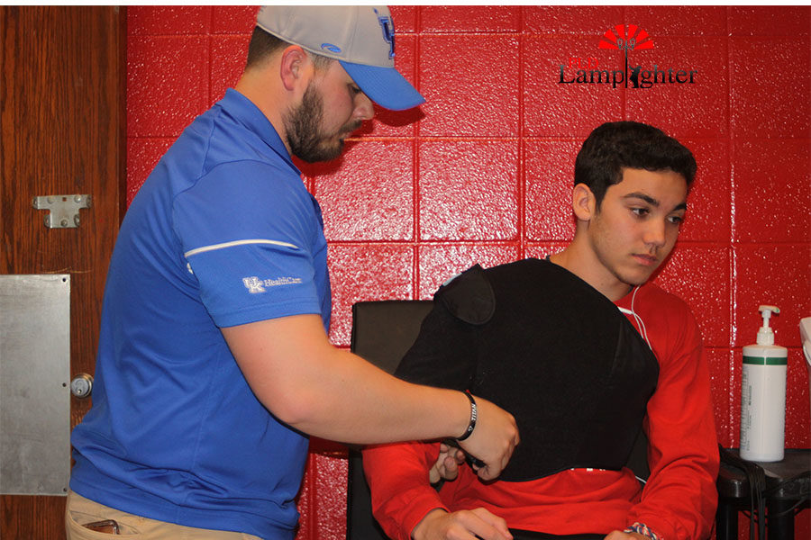 Athletic trainer Cody Begley uses the Game Ready for ice and compression to help injured athlete Landon Jackon.