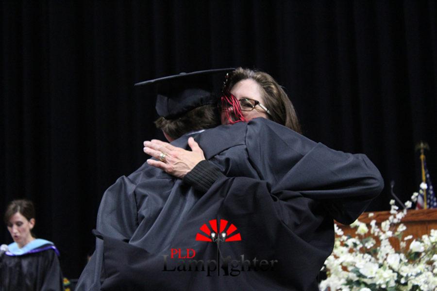 Principal Betsy Rains hugs graduating senior Jack Stokley.