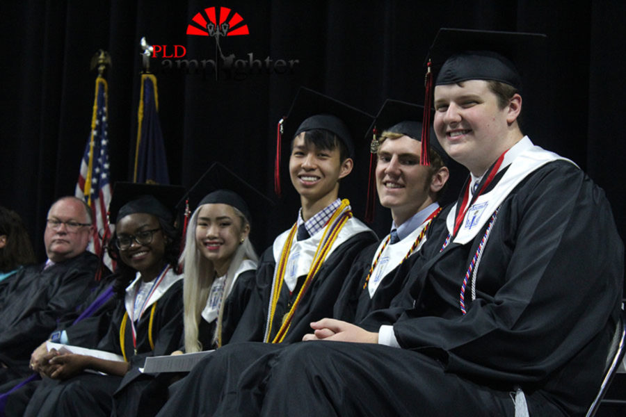 Class officers Rest Aliu, Meilin Scanish, Ben Xie, and Joey Michael smile on stage alongside Student Council President Ryan Kennedy.