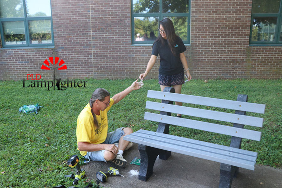 Emily Liu hands Jerome Higginbotham a piece of the bench as it nears completion.