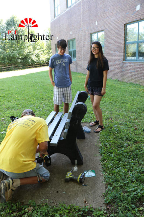 Emily Liu and Justin Kline watch Jerome Higginbotham install the bench.