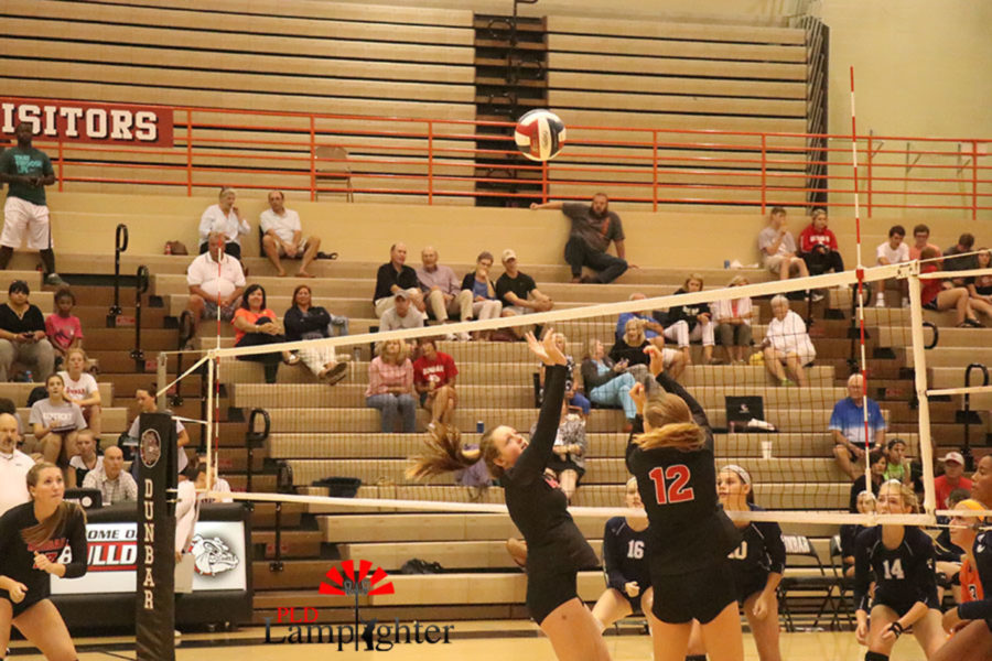 Junior Meredith Phillips (12) and freshman Kaetlin Ethington (1) get a solid touch off the block.