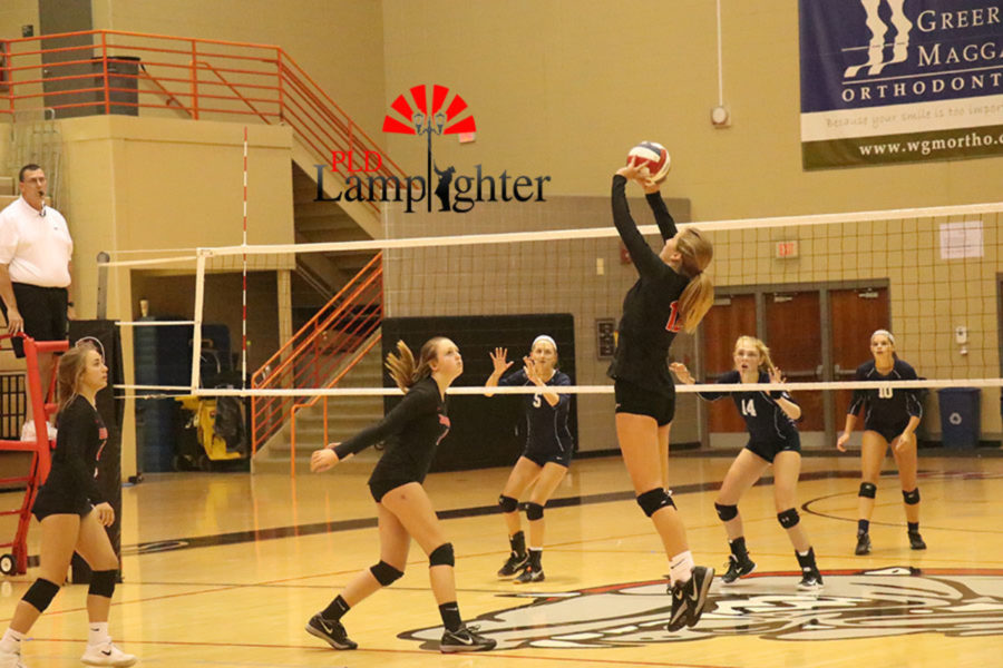 Junior Meredith Phillips assists her hitters for a kill.