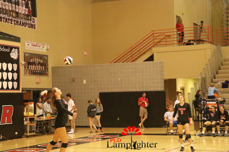 Junior Meredith Phillips (12) serves a strong ball to Boone County.