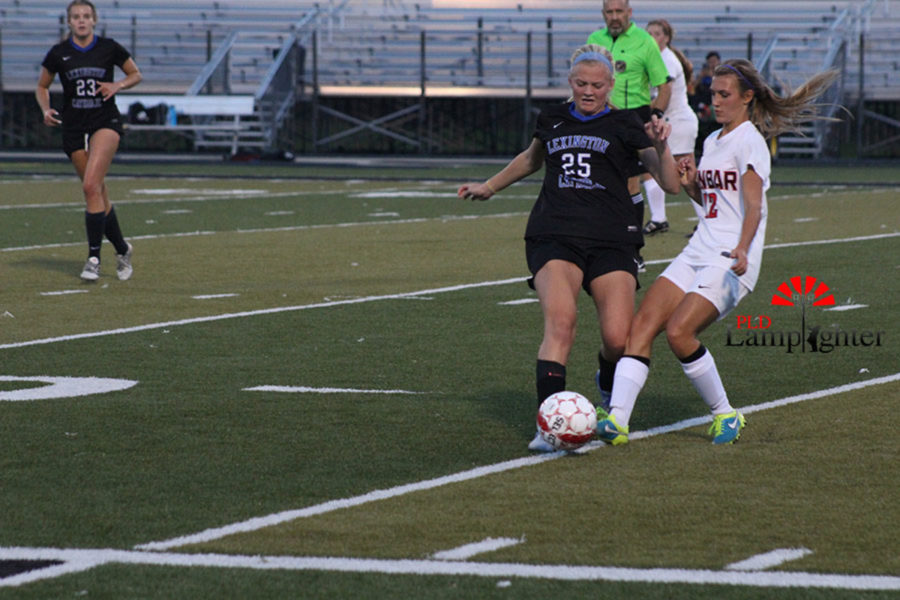 #12 Senior Baylee Lanter and a Lexington Catholic player both reach for the ball at the same time.