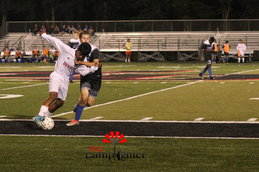 A Lexington Christian player grabs a Dunbar player who is trying to get the ball down the field towards the goal.