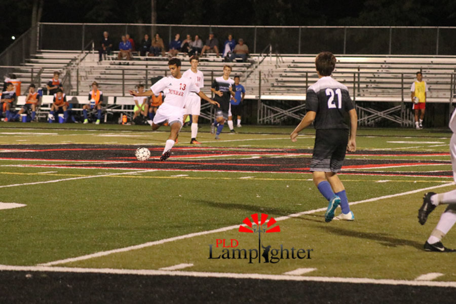 #13 Yousef Agoub has the ball and is mid-kick in efforts of launching the ball down the field towards the goal.