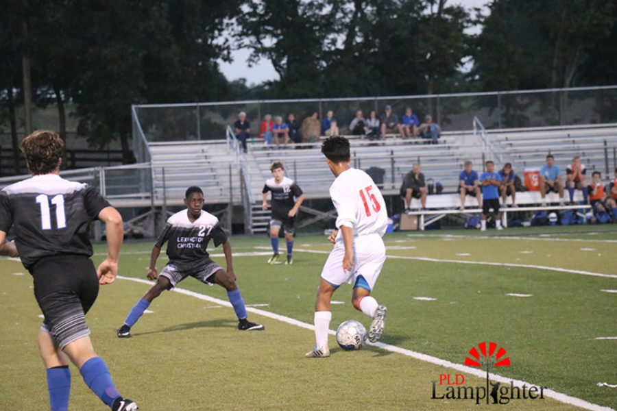 Crescencio Torres, #15 prepares to kick the ball down the field through opposing players.