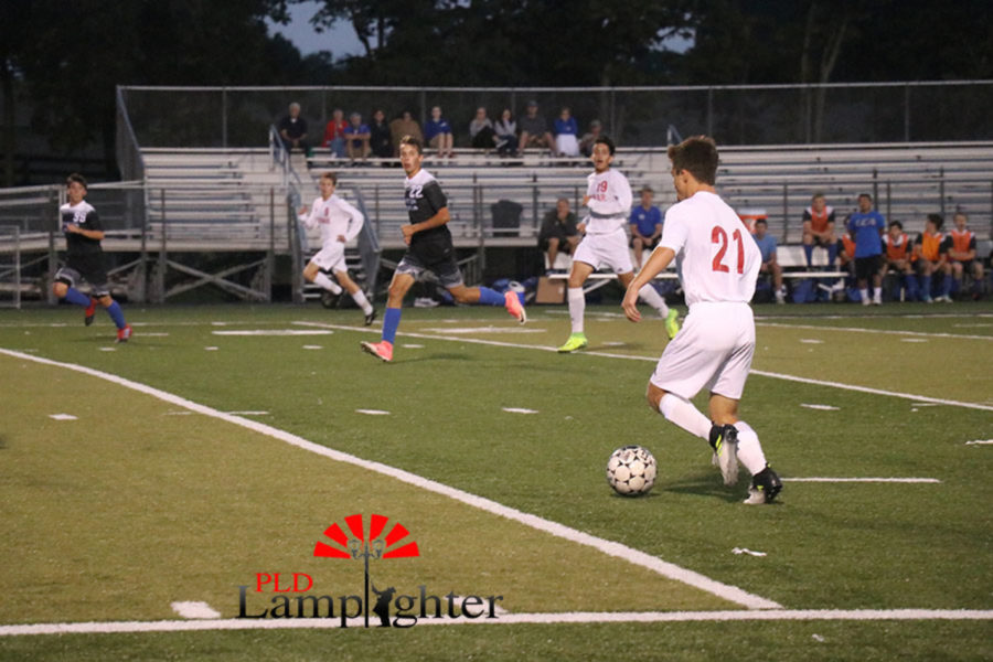 #21, Jack Rodes , dribbles the ball down the field in an attempt to score a goal.