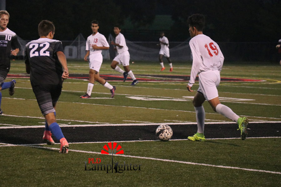 #19 Pedro Jimenez runs to the middle of the field with the ball before passing it to a teammate.
