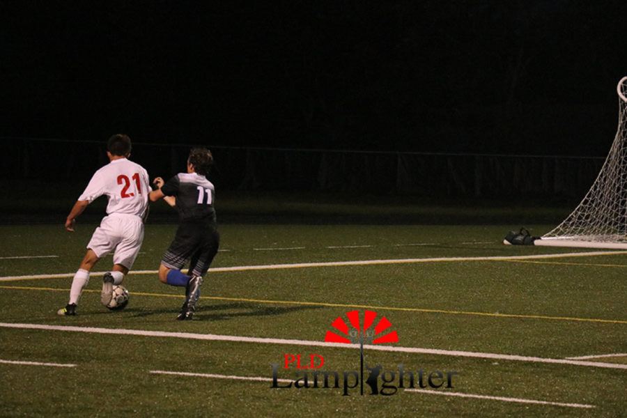 #21 Jack Rodes rushes past an opposing player trying to block him from scoring.