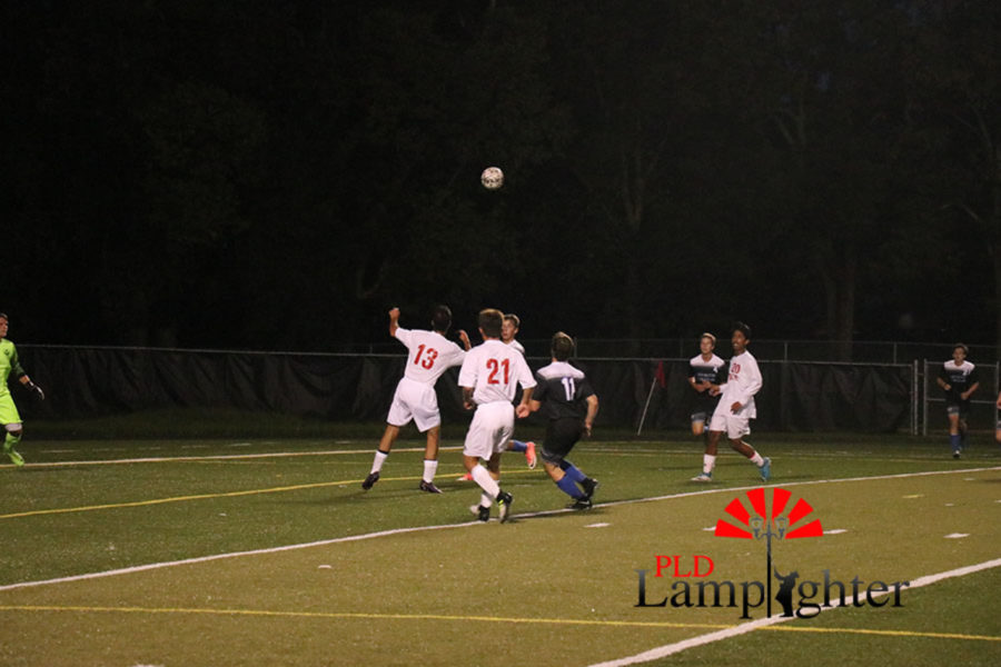 Both teams watch as the ball is mid air in an attempt to anticipate where it will land.