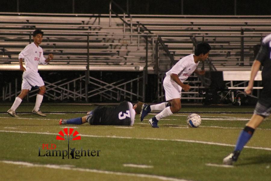 A Dunbar player runs past a fallen Lexington Christian player to make a goal as the game comes close to an end.