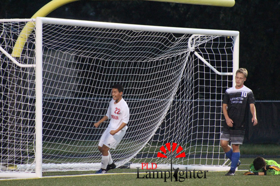 Kevin Jing, #22 is excited after a goal is scored while the opposing Lexington Christian players look defeated.