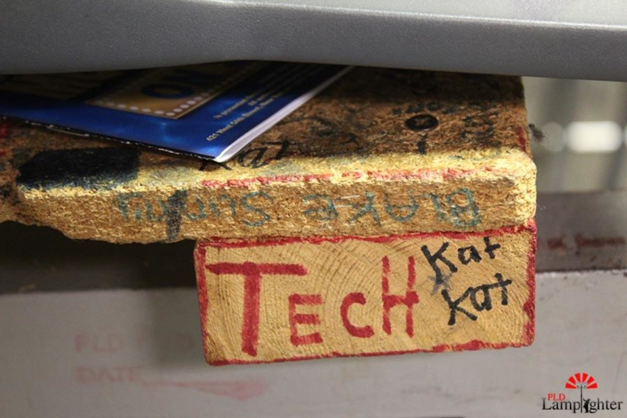 Personalized block of wood in the control room that students over the years have written on.