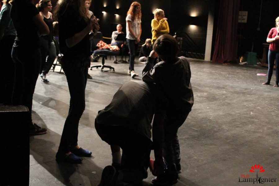 Ms. Hennings son rests off the back of an older drama student  as he ties his shoe for him.