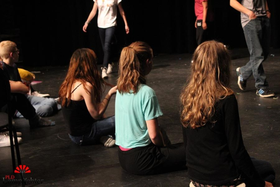 Drama students watch and study the way their partners walk so they can recreate it for an exercise.