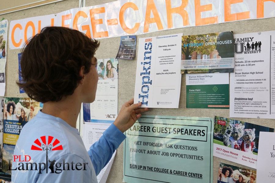 Parker Noe, Sophomore, is seen looking at the Johns Hopkins University poster.