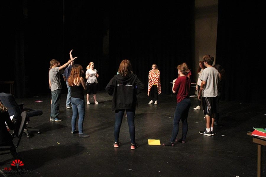 Drama students listen to instructions for an improv activity.