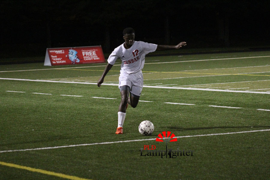 Junior Andrew Pascal dribbles the ball down the field to pass to his teammates.