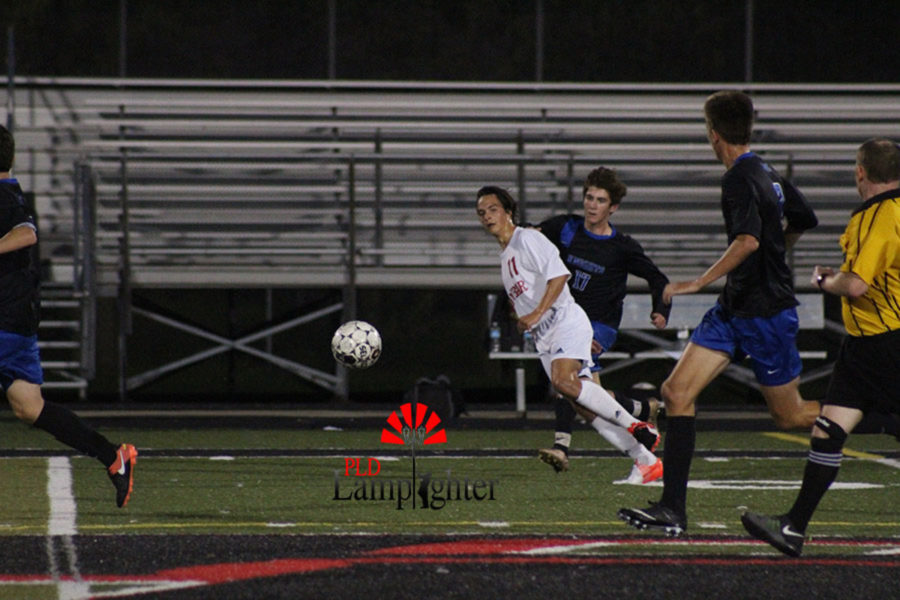 Senior Sullivan Curd hustles to get the ball from Catholic's players.