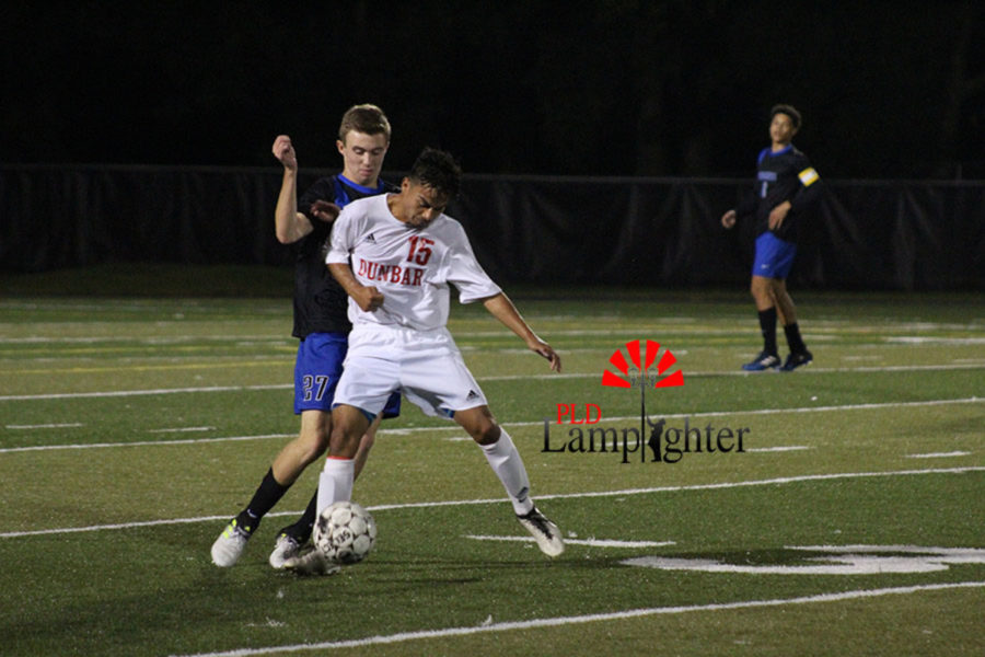 #15 Cresceino Torres aggressively takes the ball away from a Lexington Catholic player.