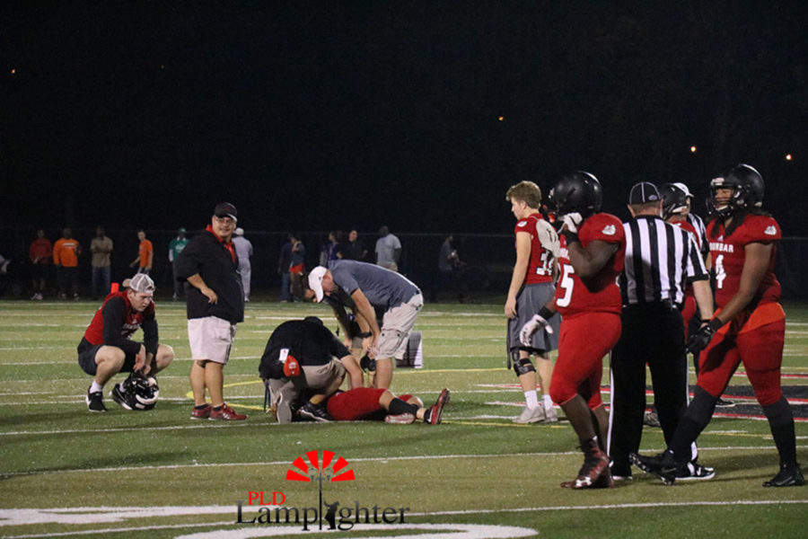 The athletic trainers help an injured Dunbar player.