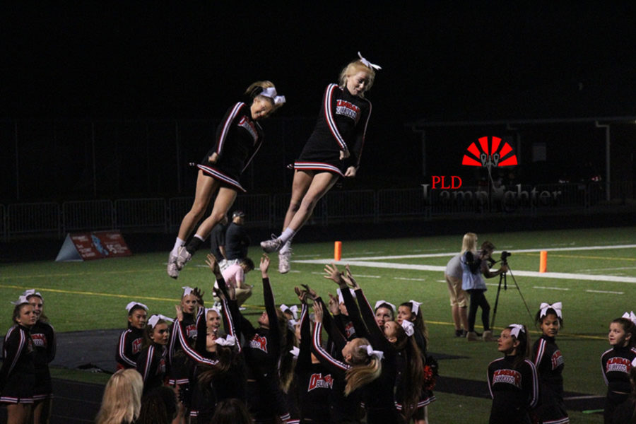 Cheerleaders Natalie Rowe (left) and Julia Beard (right) dismount from a stunt