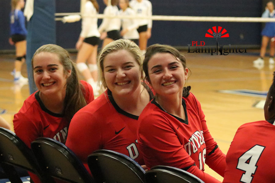 Macy Jundi, Emma Berger, and Hannah Tucker (left to right) are excited for the first district game of the season.