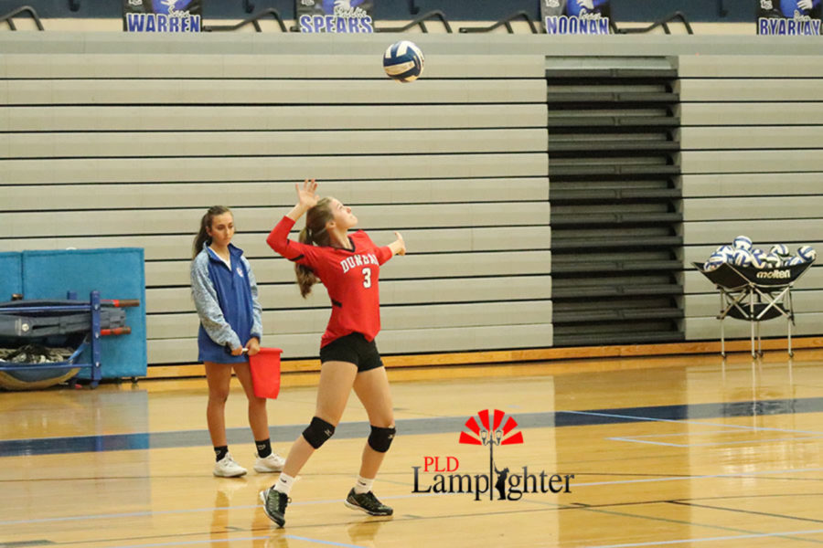 #3 Caroline Cole serves the ball to score the point.
