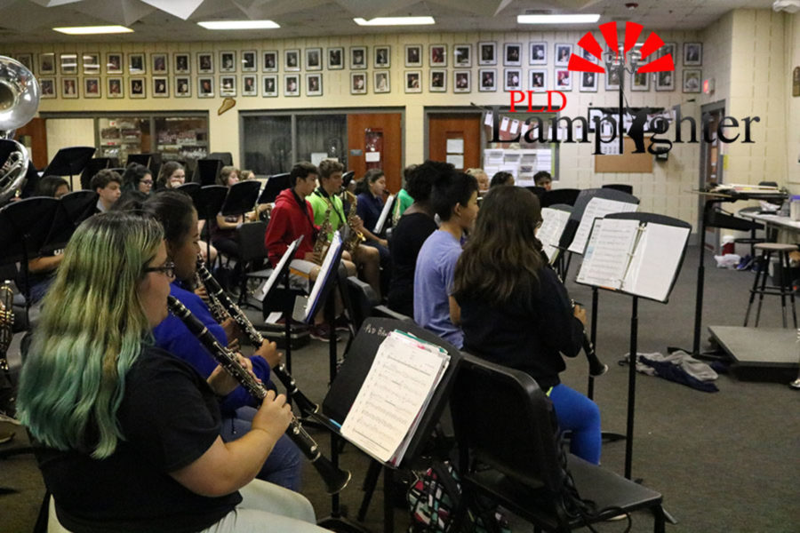 The saxophones and clarinets practicing one of their songs for concert band.