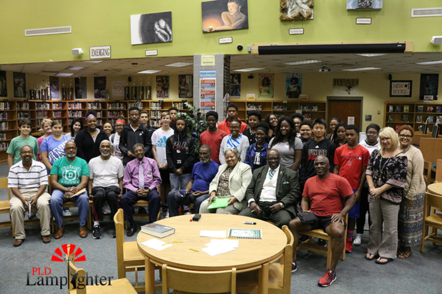 Dunbar students involved in the Leaders in the Making program pose for a picture with Dunbar Alumni members.