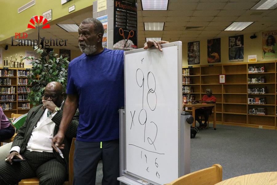 Mr. Richard Green shows students a short cut for solving a math problem.