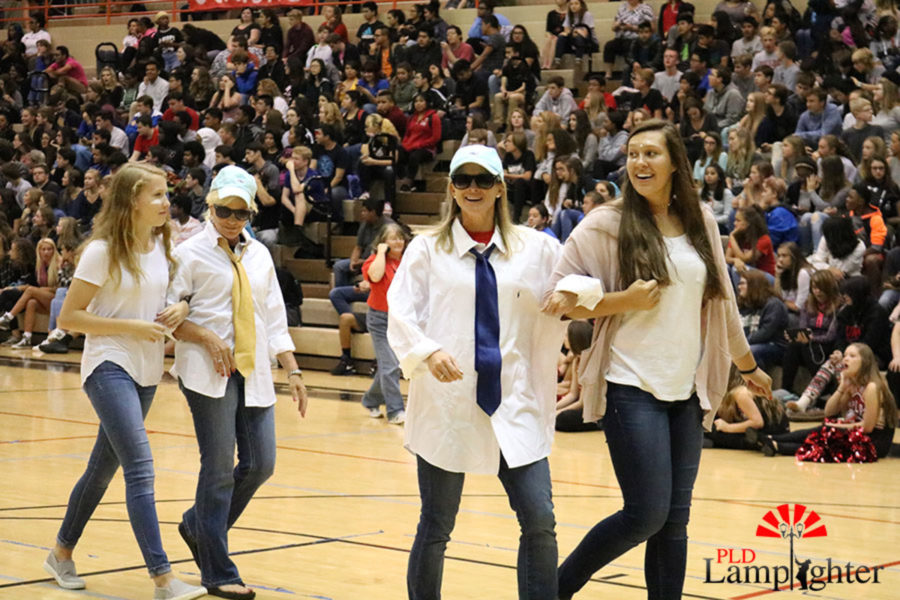 Sophomores Peyton Gash and Abigail Layne escort Mrs. Martin and Coach Morgan in the spirit week fashion show.