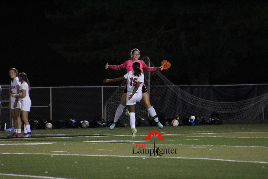 #1 Morgan Turcotte and #15 Meron Roach chest bump to build hype before the game.