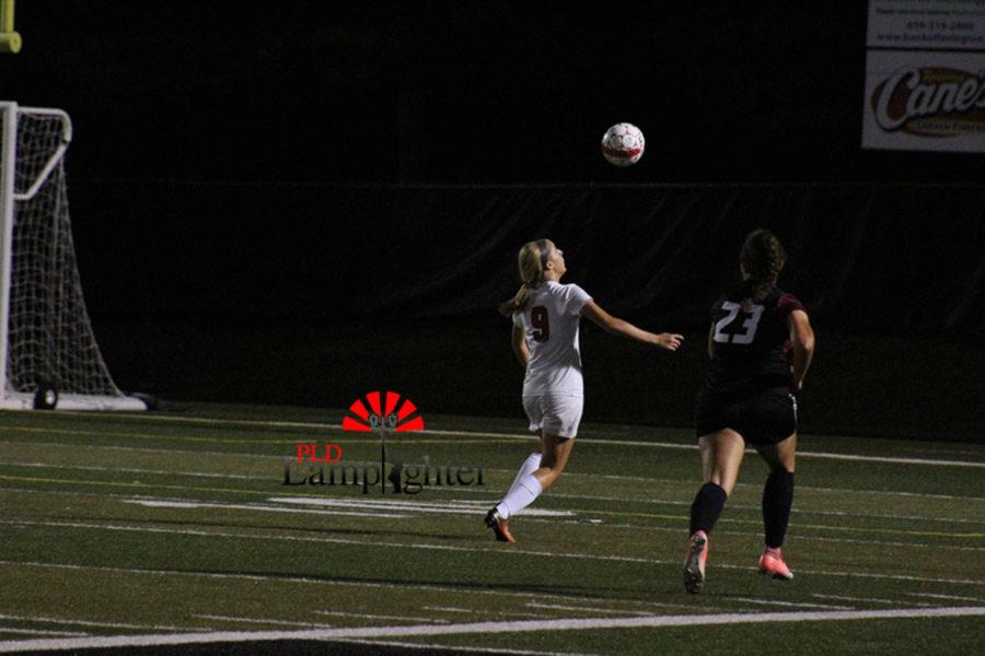 #9 Senior Elizabeth Lippert prepares to head-butt the soccer ball.