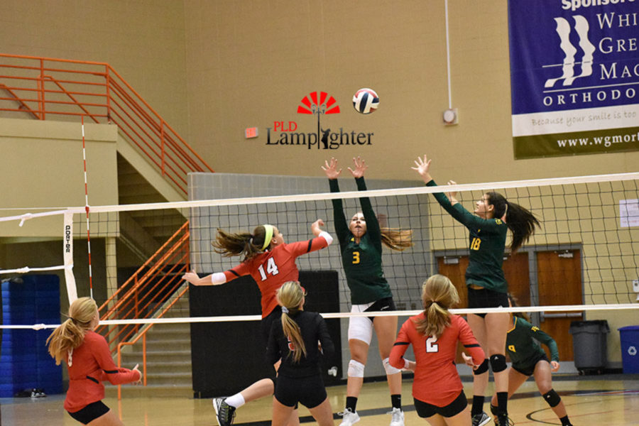 #14 Sophomore Eleanor Davis leaps up, attempting to return the ball across the net.