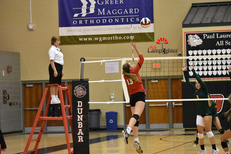 #13 Senior Virginia Smith jumps up to swing the ball.
