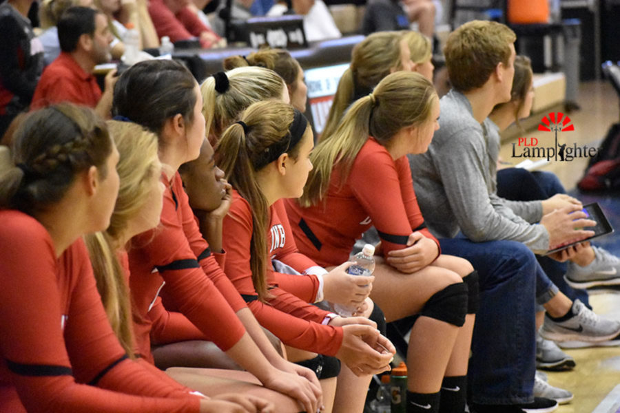 Dunbar volleyball players watch as their teammates perform a strong game against Bryan Station.
