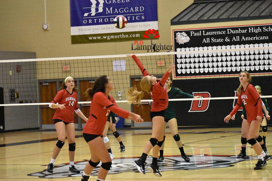 #11 Savannah Dudek prepares to serve the ball as #8 Olivia Stotz misses the ball flying overhead.