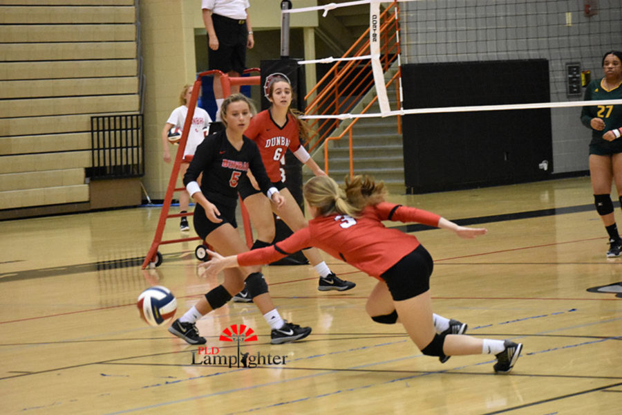 #3 Freshman Caroline Cole  reaches for the ball as it falls to the ground.