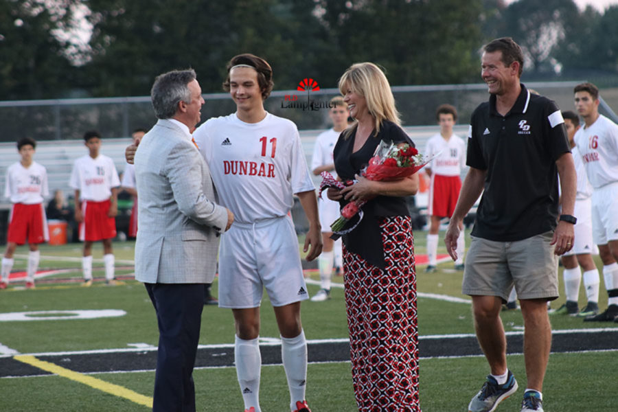 Senior+Sullivan+Curd+being+congratulated+by+his+parents+on+senior+night.