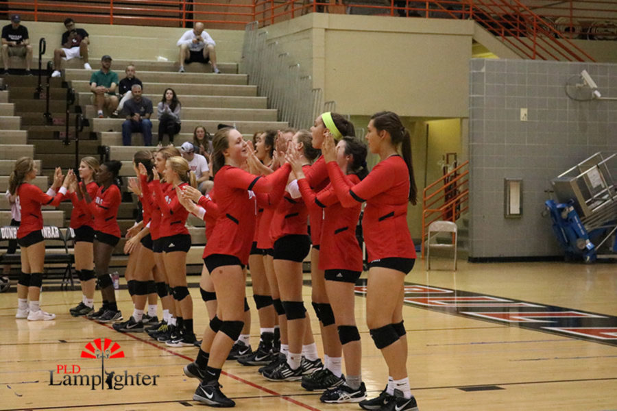 Freshman Kaetlin Ethington receives high-fives by her teammates to get hyped for the game.