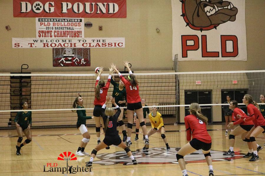 #6 Senior Macy Jundi and #14 Sophomore Eleanor Davis block the oncoming volleyball.