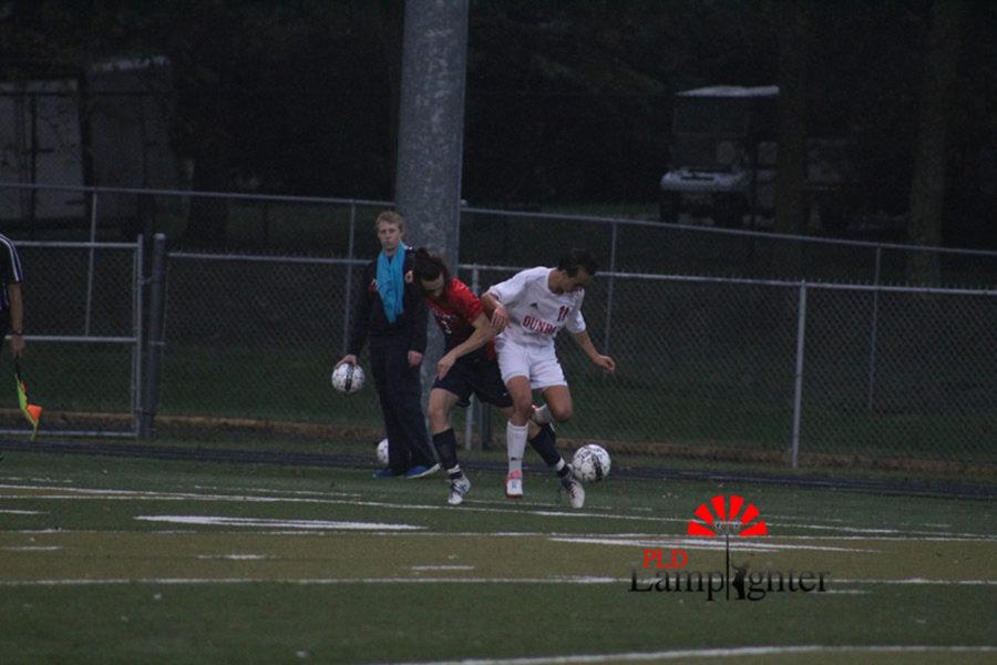 #11 Senior Sullivan Curd struggles against the opposing team fro possession of the ball.
