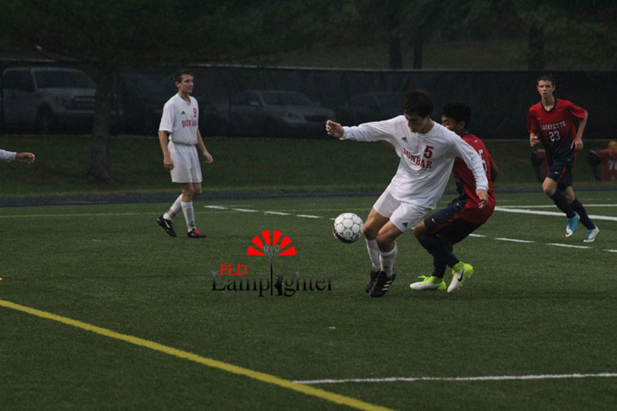 #5 Senior Jackson Akins holds off player from the opposing team.
