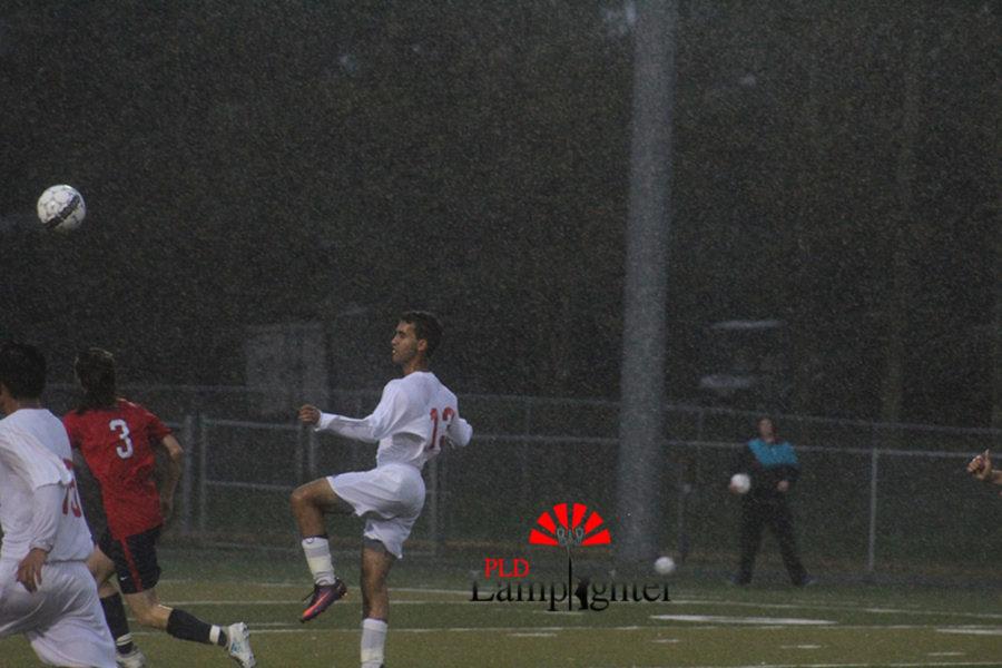#13 Senior Yousef Agoub heads the ball forward.