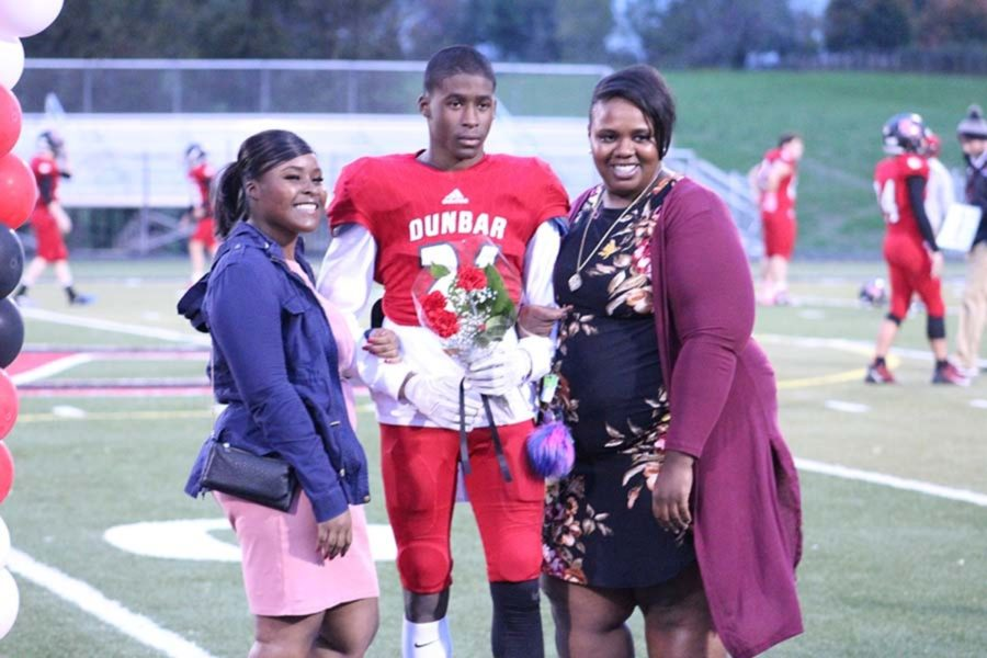 Senior Football player Chiani Russell and his family posing for a photo.
